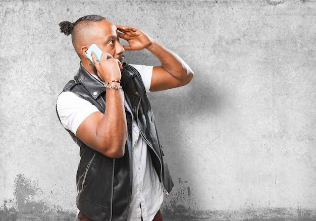 Homem que fala no telefone com a mão na testa Foto gratuita