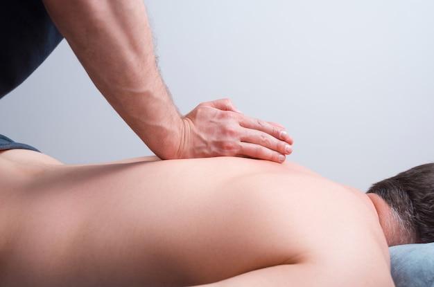 Homem que faz a cinesiologia fazer massagens no fundo branco. Foto Premium