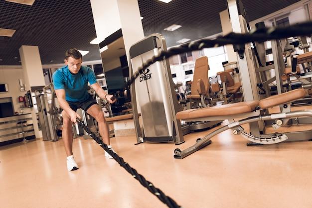 Homem que faz o exercício com cordas no gym. Foto Premium