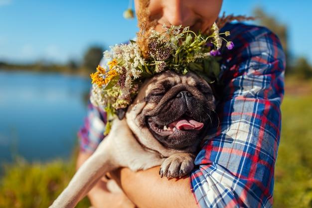 Homem que guarda o cão do pug com a grinalda da flor na cabeça. homem andando com animal de estimação pelo lago de verão Foto Premium