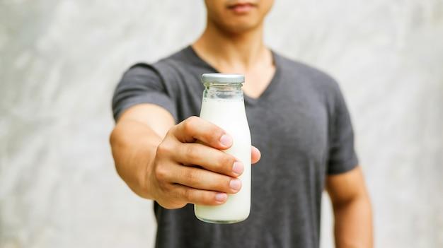 Homem que guarda uma garrafa do leite no fundo cinzento. Foto Premium