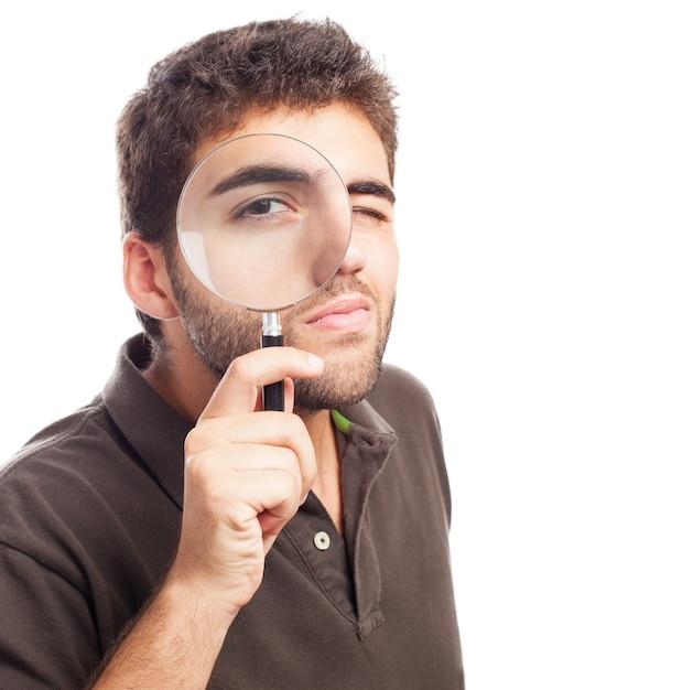 Homem que olha através de uma lupa Foto gratuita