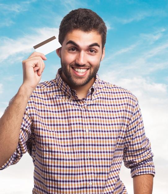 Homem que prende o cartão de crédito em mãos. Foto gratuita