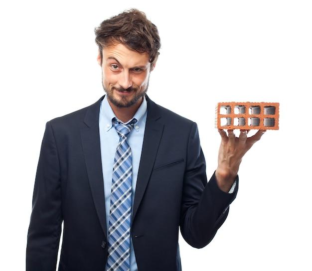Homem que prende um tijolo Foto gratuita