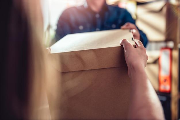 Homem que recebe o pacote do correio Foto Premium