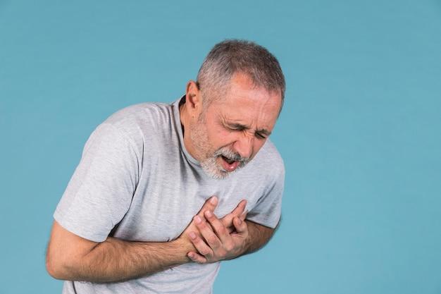 Homem que sofre de dor no peito em pano de fundo azul Foto Premium