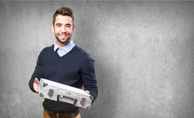 Homem que sorri com uma maleta metálica Foto gratuita