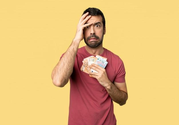 Homem que toma muito dinheiro com surpresa e expressão facial chocada no fundo amarelo isolado Foto Premium