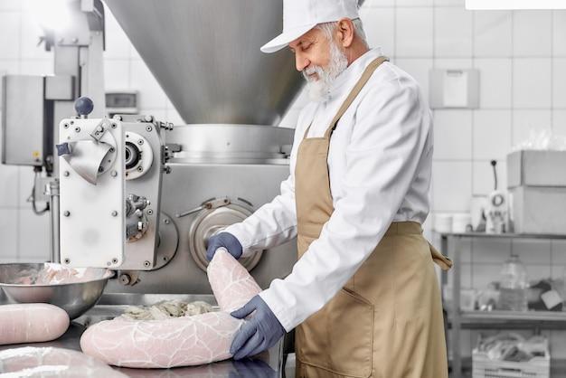 Homem que trabalha com equipamentos para produção de salsichas. Foto Premium