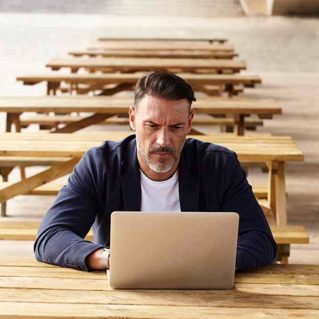 Homem que trabalha com o computador ao ar livre Foto gratuita