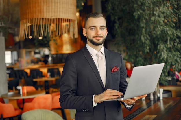 Homem que trabalha com um laptop na mesa Foto gratuita