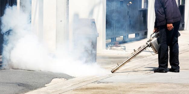 Homem que trabalha com uma máquina de fumaça no bueiro para controle de pragas Foto Premium
