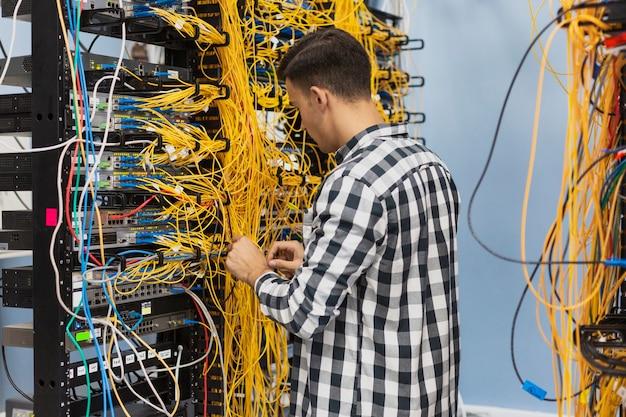 Homem que trabalha em um switch ethernet Foto gratuita