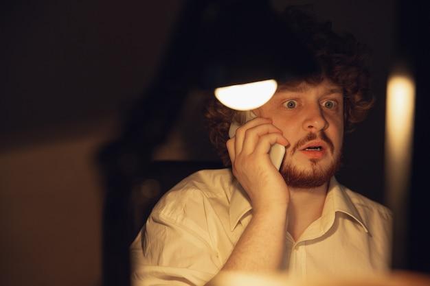 Homem que trabalha no escritório sozinho durante o coronavírus ou a quarentena de covid-19, ficando até tarde da noite Foto gratuita