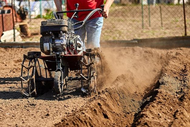 Homem que trabalha no jardim com garden tiller. leme de jardim para trabalhar, close-up. Foto Premium