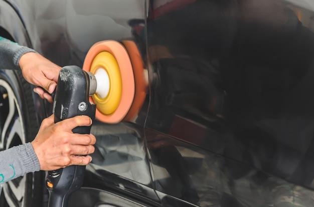 Homem que trabalha para o polimento, revestimento de carros. Foto Premium