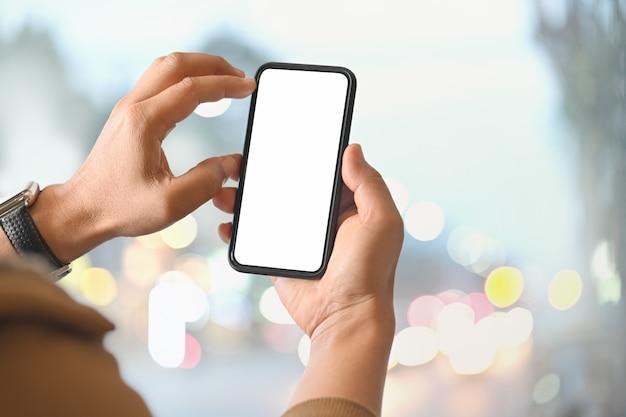 Homem que usa o telefone esperto sobre o fundo brilhante borrado Foto Premium