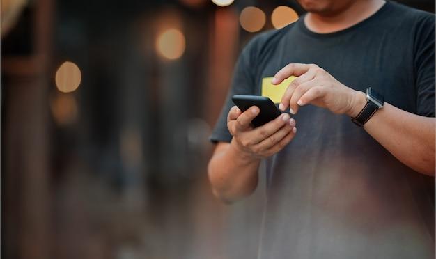 Homem que usa o telemóvel na noite da rua. Foto Premium