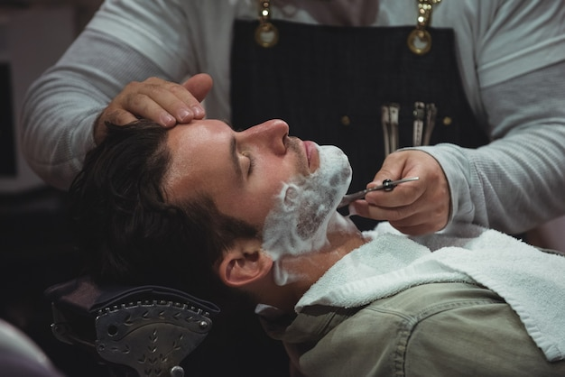 Homem raspando a barba com navalha Foto gratuita
