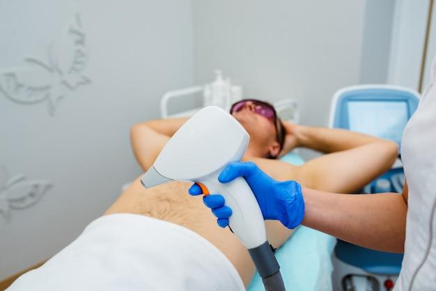 Homem recebendo depilação a laser na axila do centro de beleza Foto Premium