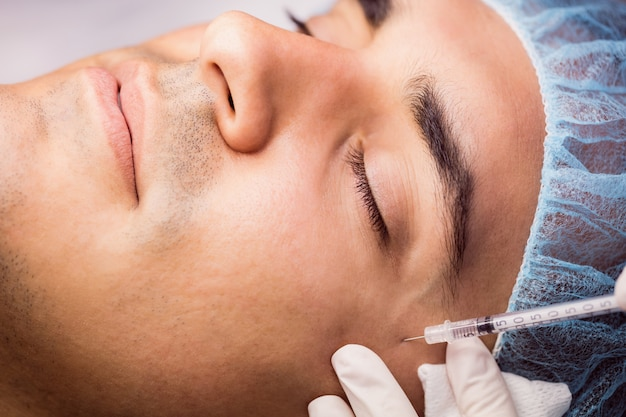 Homem recebendo injeção de botox no rosto Foto gratuita