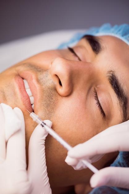 Homem recebendo injeção de botox nos lábios Foto gratuita
