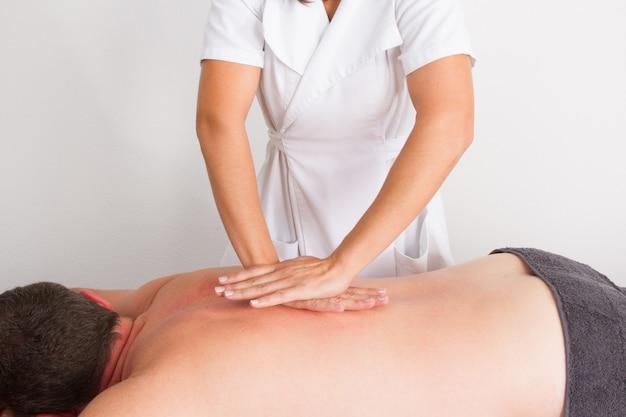Homem recebendo massagem nas costas no salão spa Foto Premium
