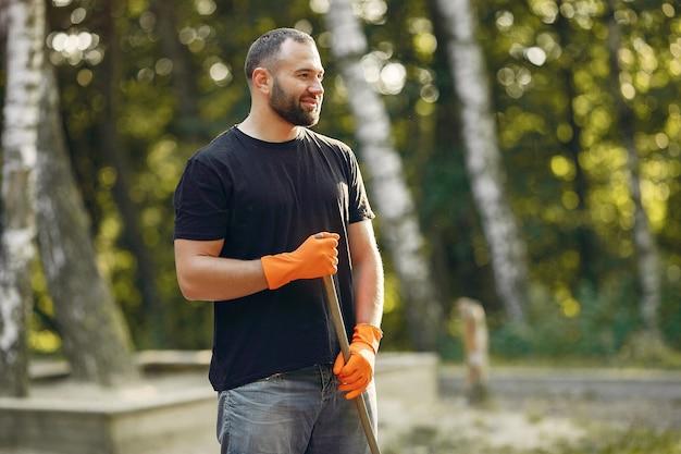 Homem recolhe folhas e limpa o parque Foto gratuita