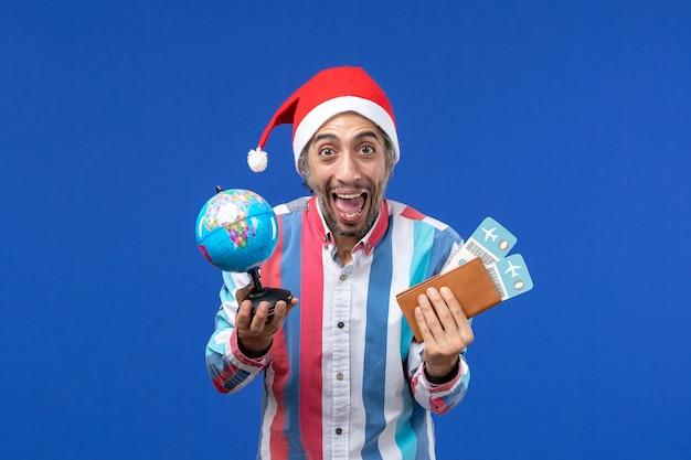 Homem regular de vista frontal com globo e ingressos na parede azul emoções feriado ano novo Foto gratuita
