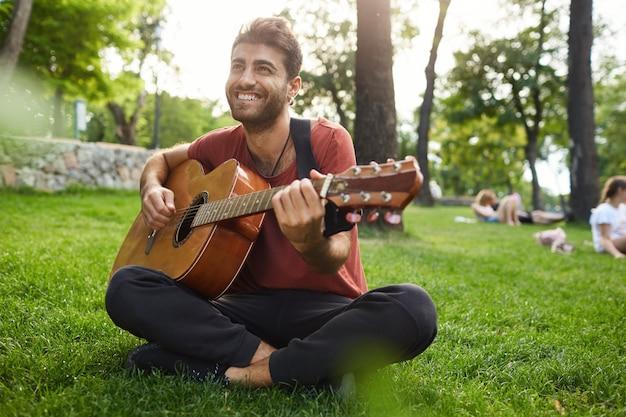 Homem relaxado e sonhador tocando violão, sentado na grama no parque com um instrumento Foto gratuita