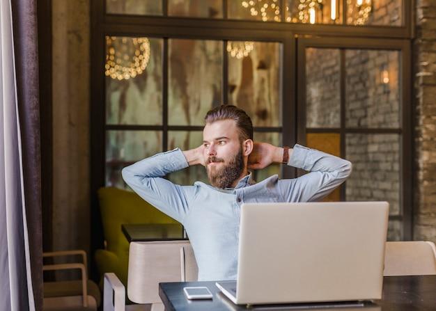 Homem relaxado sentado no restaurante com laptop e celular na mesa Foto gratuita