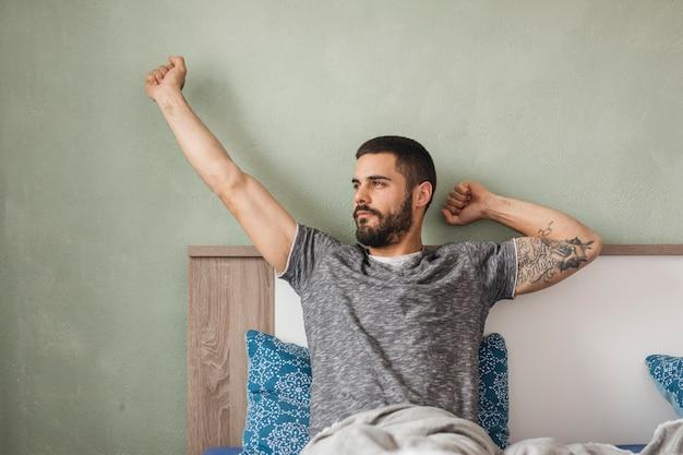 Homem, relaxante, em, seu, cama Foto gratuita