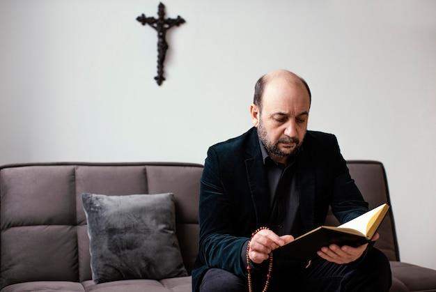 Homem religioso lendo um livro sagrado em casa Foto Premium