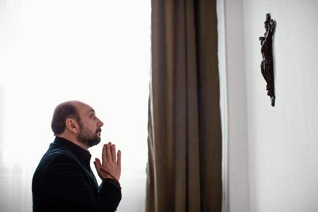 Homem religioso rezando em casa Foto Premium