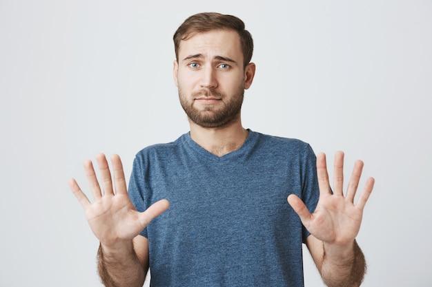 Homem relutante, apertando as mãos em recusa, rejeitar oferta Foto gratuita