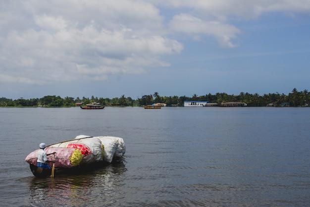 Homem remando uma canoa de madeira cheia de plástico Foto gratuita