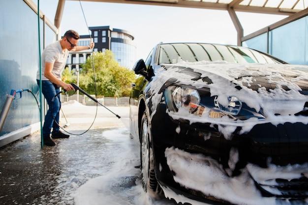 Homem removendo a espuma de um carro Foto Premium