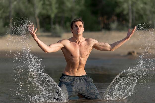 Homem, respingue água, em, praia Foto gratuita