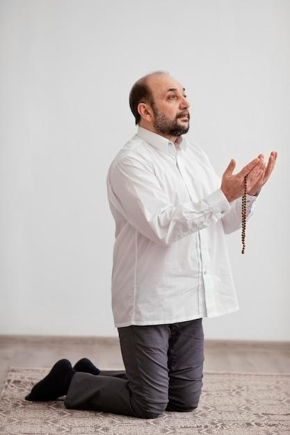 Homem rezando no chão dentro de casa Foto gratuita
