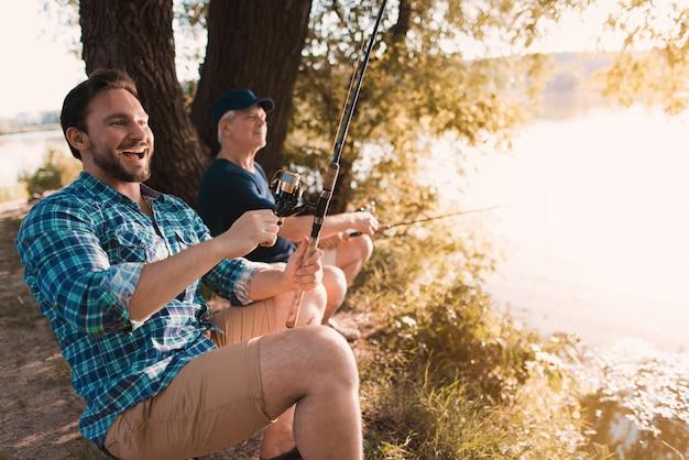 Homem ri e se prepara para retirar o peixe Foto Premium
