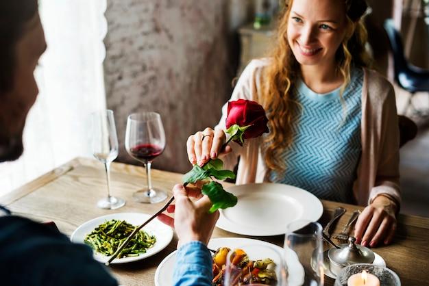 Homem romântico dando uma rosa para mulher em uma data Foto Premium