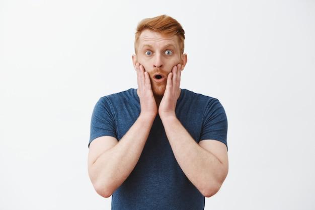 Homem ruivo atraente, caucasiano, com cerdas expressando surpresa e espanto, tocando o rosto e fechando os lábios, em estado de estupor e olhos estalados, sob impressão Foto gratuita
