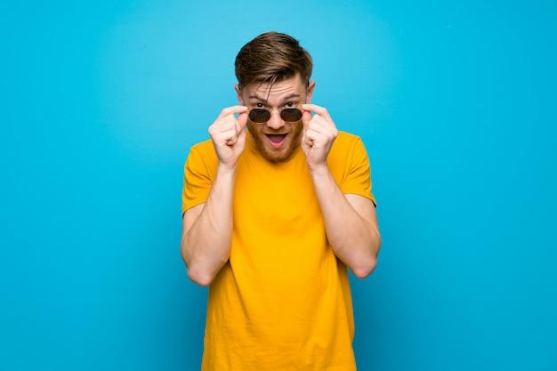 Homem ruivo azul muro com óculos e surpreso Foto Premium