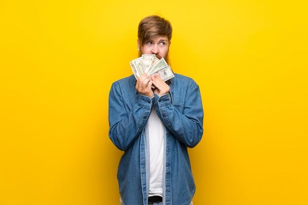 Homem ruivo com barba longa ao longo da parede amarela isolada, levando muito dinheiro Foto Premium