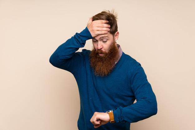 Homem ruivo com barba longa ao longo da parede isolada com relógio de pulso e surpreso Foto Premium