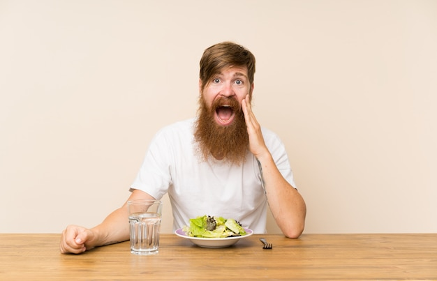 Homem ruivo com barba longa e com salada com surpresa e expressão facial chocada Foto Premium