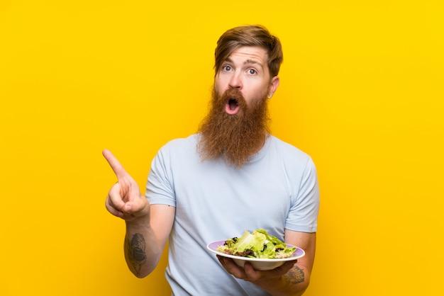 Homem ruivo com barba longa e salada sobre parede amarela isolada surpreendeu e apontando o lado Foto Premium