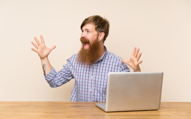 Homem ruivo com barba longa em uma mesa com um laptop com expressão facial de surpresa Foto Premium