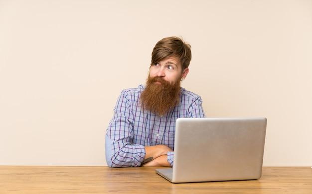 Homem ruivo com barba longa em uma mesa com um laptop em pé e olhando para o lado Foto Premium