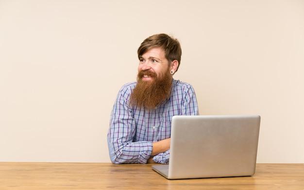 Homem ruivo com barba longa em uma mesa com um laptop rindo Foto Premium